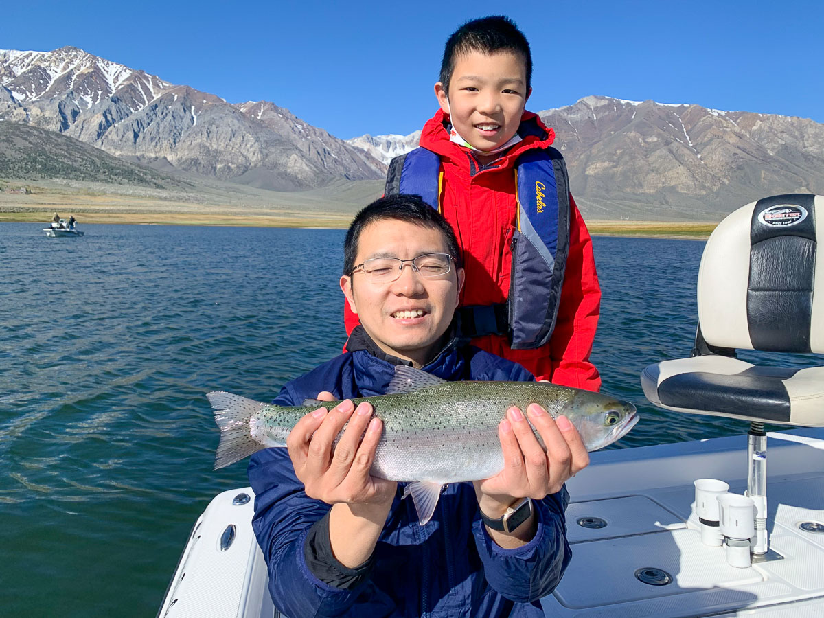 A father and son fly fishing team with a large rainbow trout from a mountain lake in the eastern sierra.