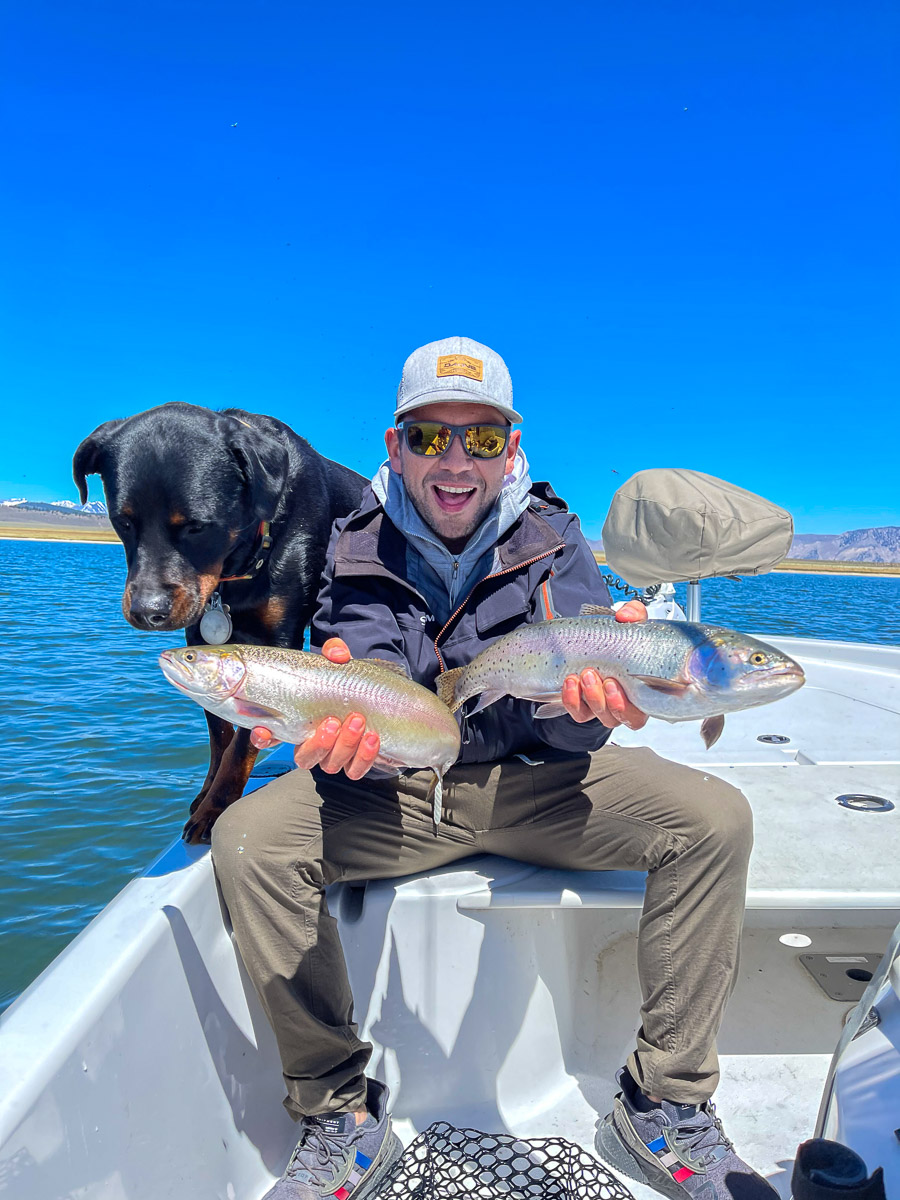 A young fly fisherman and a rottweiler dog inspecting a couple of rainbow and cutthroat trout while on a boat on a lake.
