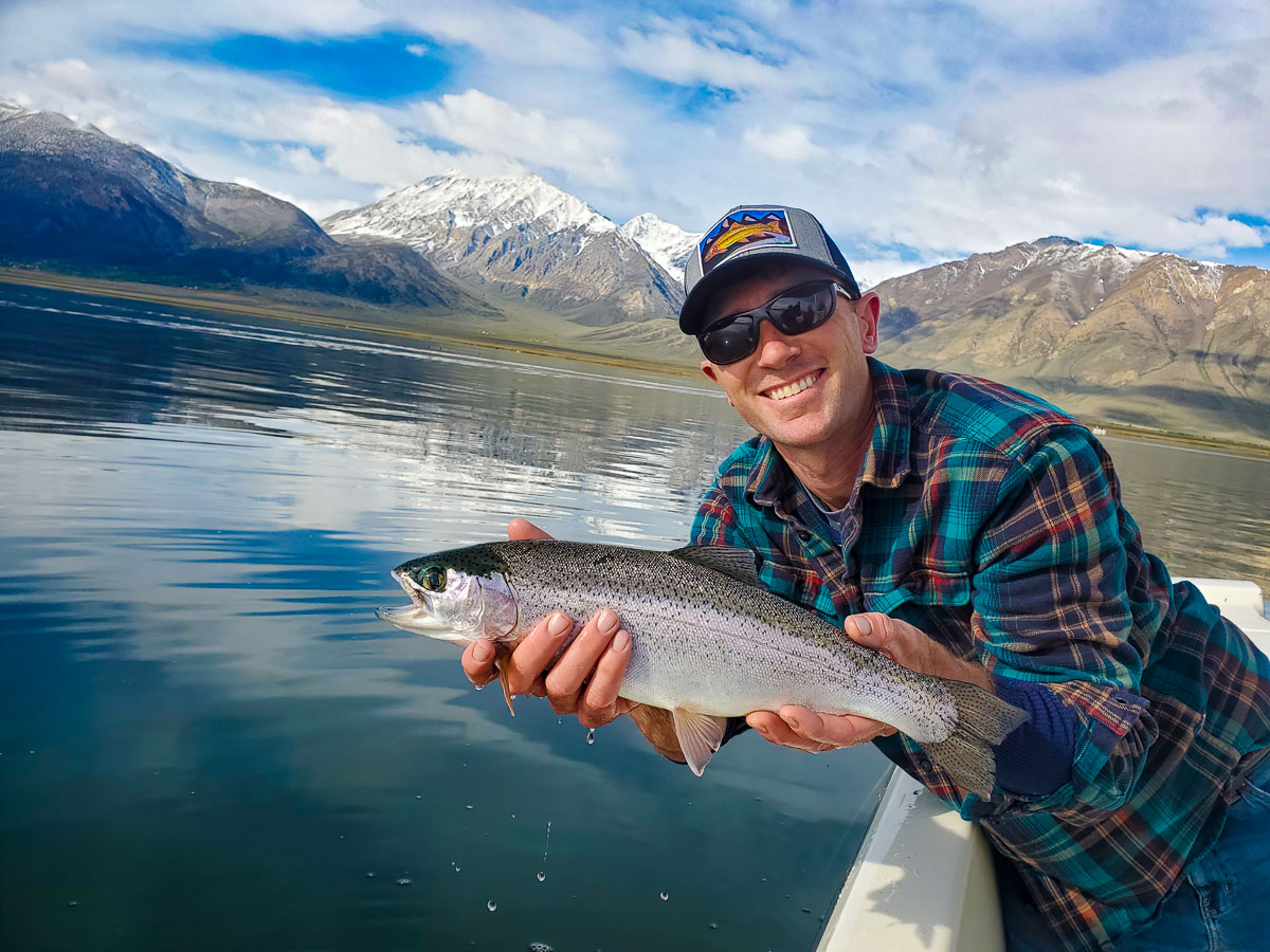 A man holding a large rainbow trout on a lake.