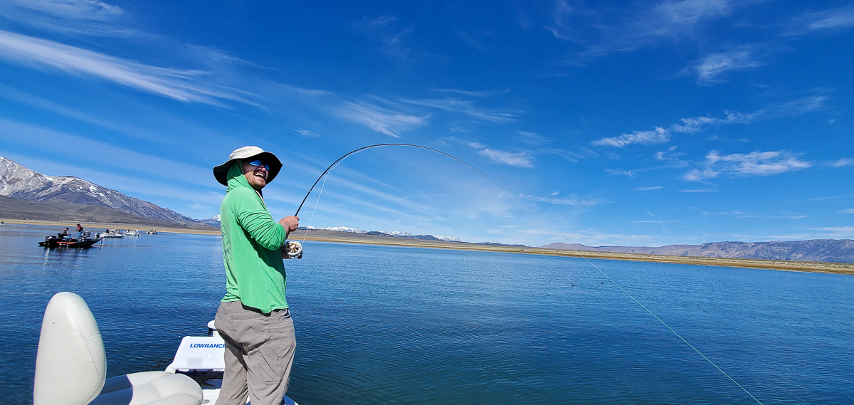 A fly fisherman reeling in a trout on a lake with mountains in the background.