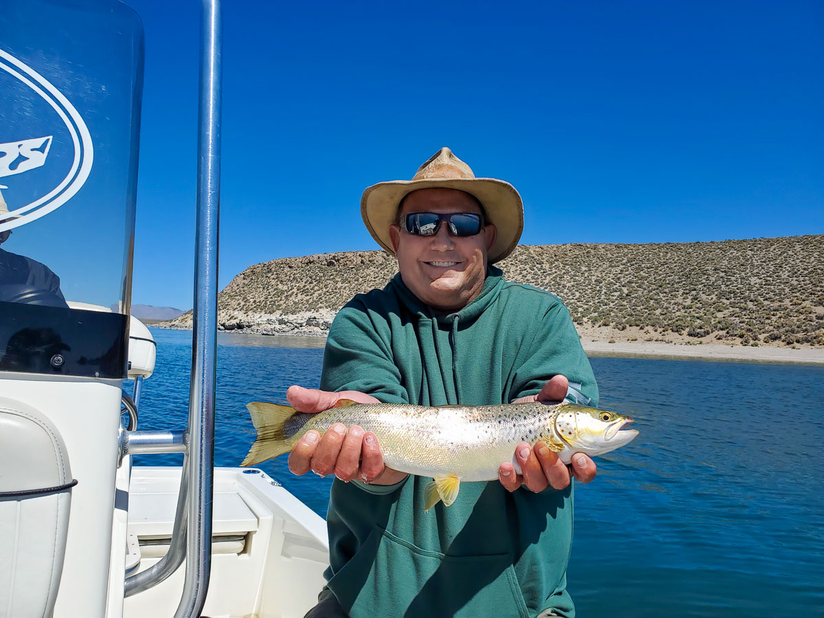 A fly fisherman with a wide-brim hat holding a cutthroat trout on a lake.