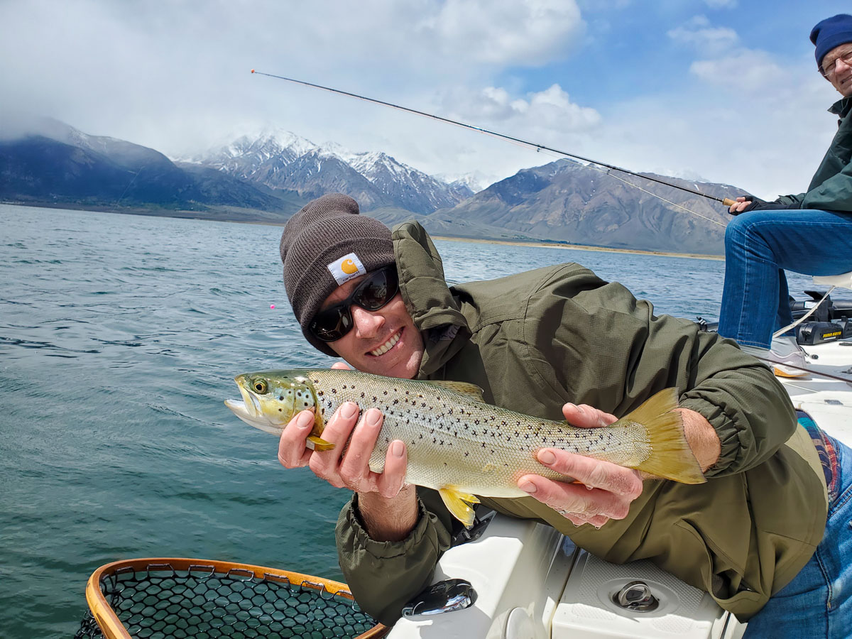 A man holding a large brown trout on a lake.