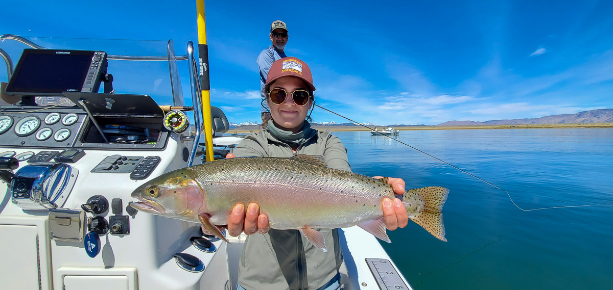 A lady fly fisher holding a huge cutthroat trout on a lake with another angler fishing behind her.