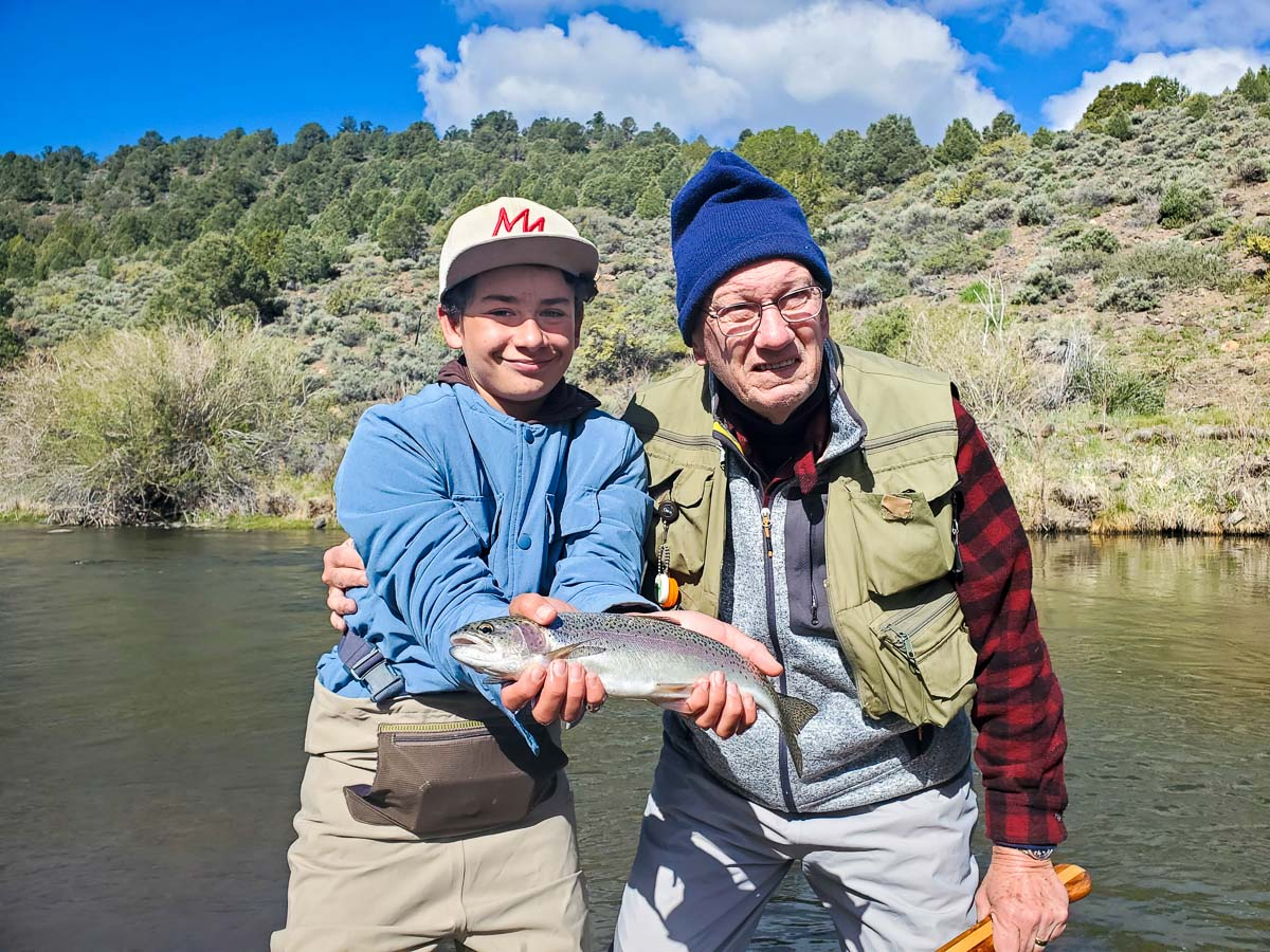 An elderly man hugging a young boy holding a rainbow trout on a river.