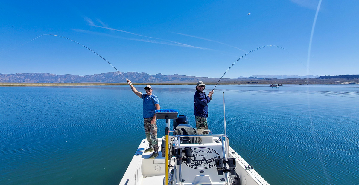 A pair of fly fishermen hooked up to trout and the same time in a boat on a mountain lake.