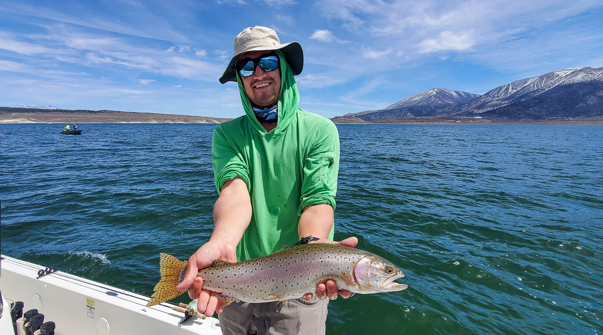 A smiling angler with a lime green shirt holding a cutthroat trout from Crowley Lake.