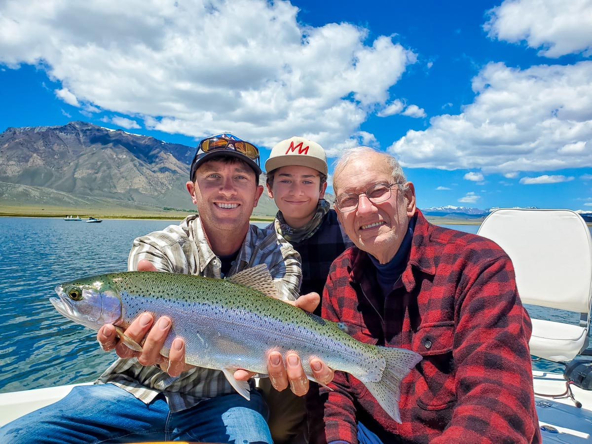 A trio of people holding a large rainbow trout on a lake.