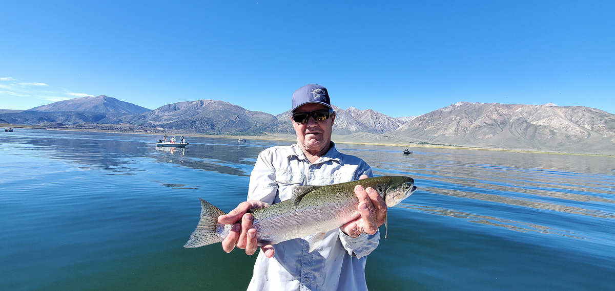 A fly fisheman holding a big rainbow trout in a boat on a lake.