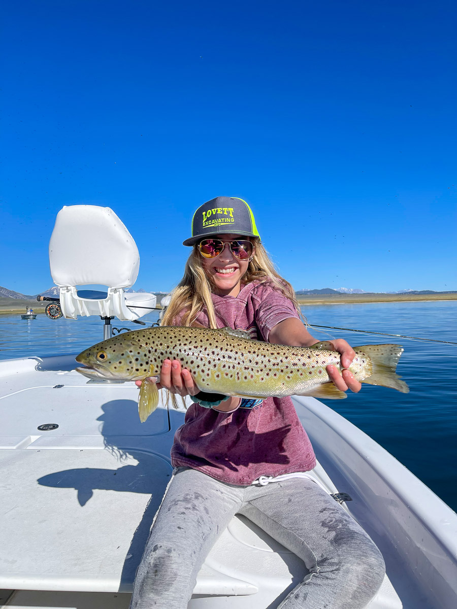 A young girl with a grey hat holding a large cutthroat trout in a boat on a lake.