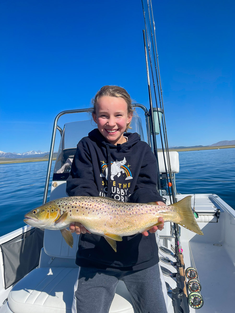 A young girl with blonde hair holding a trophy brown trout in a boat on a lake.