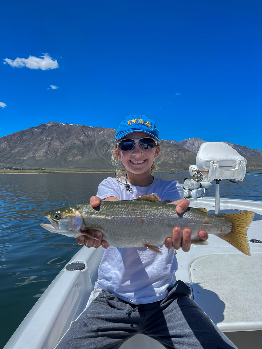 A youth girl with a blue UCLA hat holding a cutthroat trout from a lake on a boat.