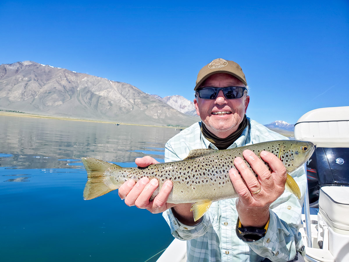A smiling fly fisherman holding a brown trout on a lake in a boat.