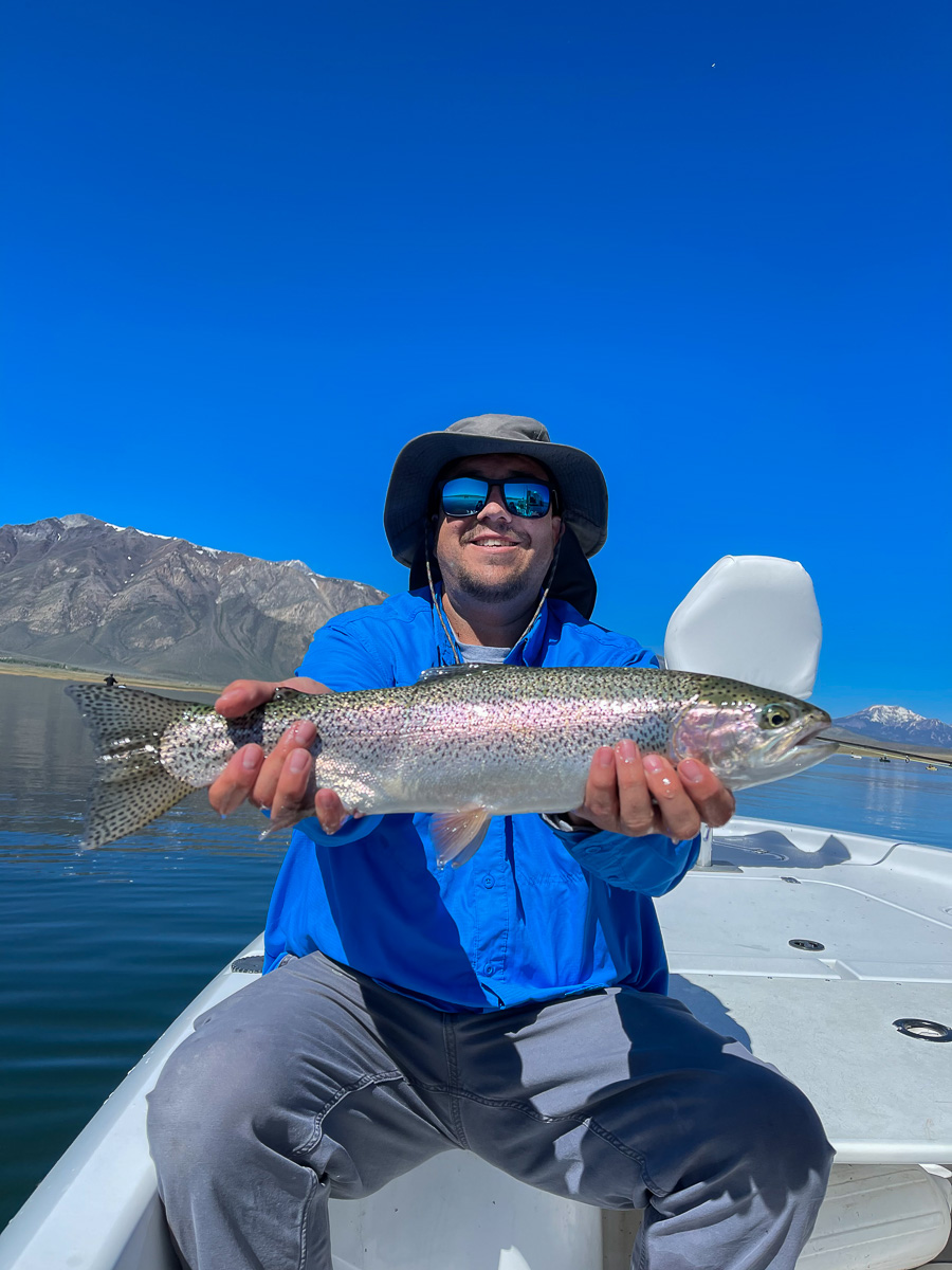 A fly fisherman holding a rainbow trout on a lake in a boat.