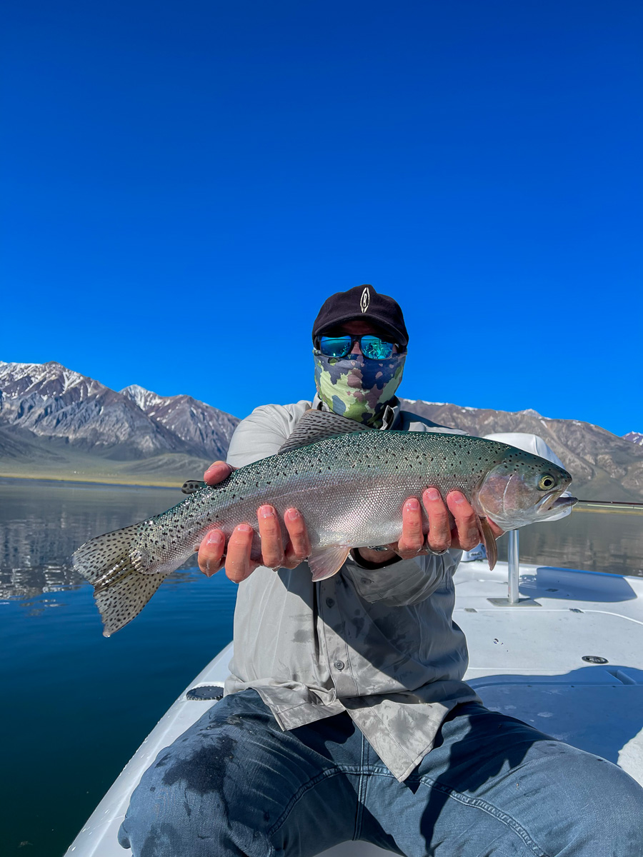 A masked fly fisherman holding a rainbow trout on a lake in a boat.