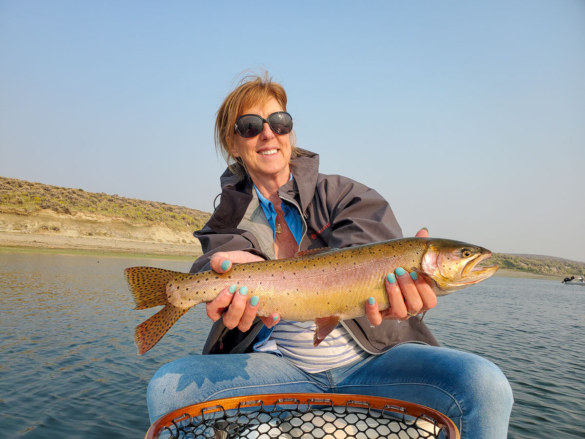A female angler holding a large cutthroat trout on a lake.