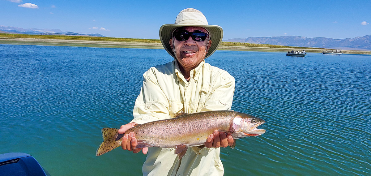 A smiling fly fisherman holding a cutthroat trout on a lake in a boat.