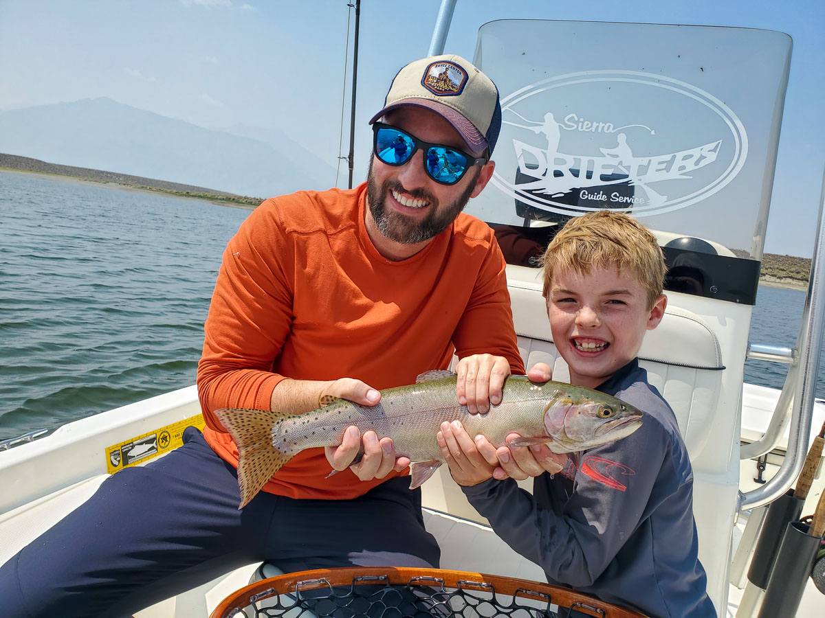 A smiling fly fisherman and a young boy holding a cutthroat trout on a lake in a boat.