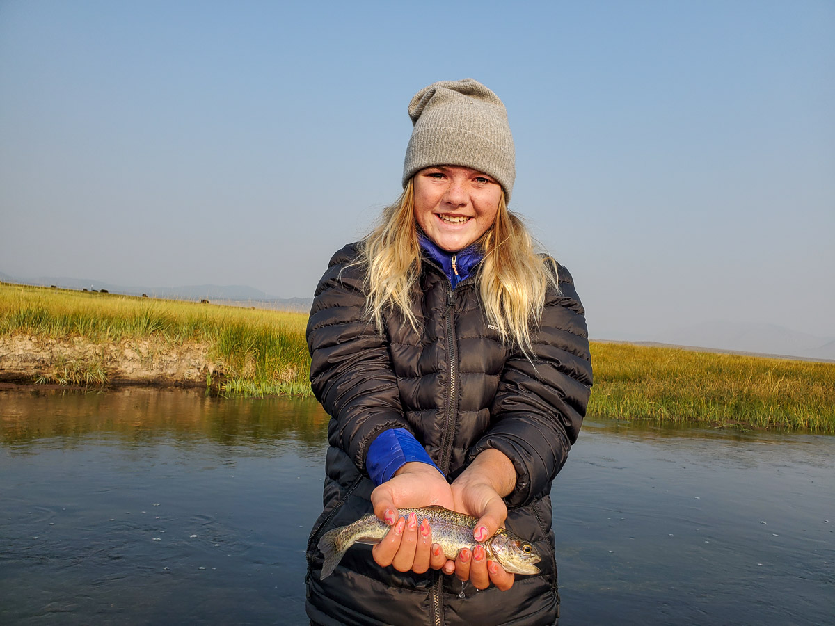 A young girl holding a rainbow trout while standing in a river with tall green grass on the banks.
