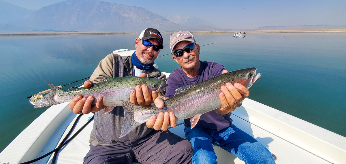 A pair of smiling fly fisherman holding a pair of rainbow trout on a lake in a boat.