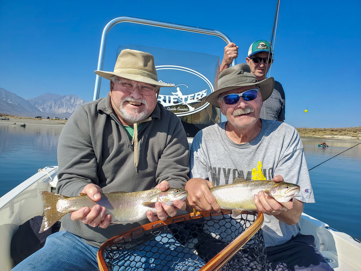 A pair of smiling fly fisherman holding 2 rainbow trout on a lake in a boat.