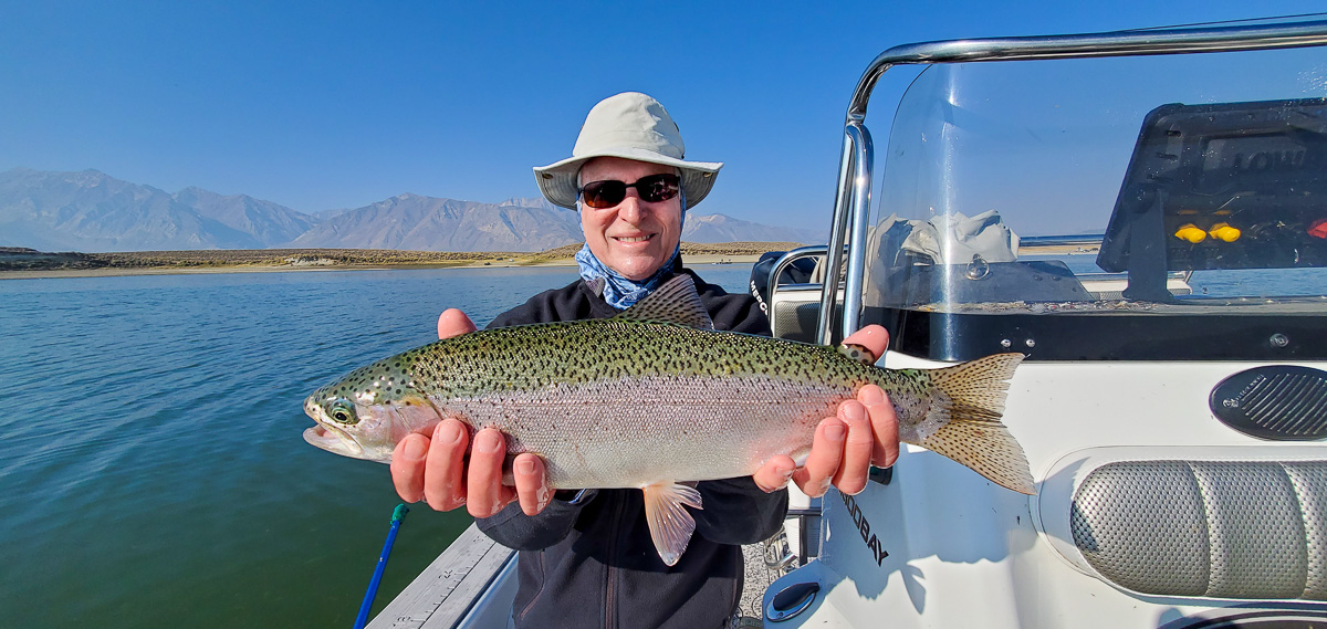 A smiling fly fisherman holding a rainbow trout on a lake in a boat.