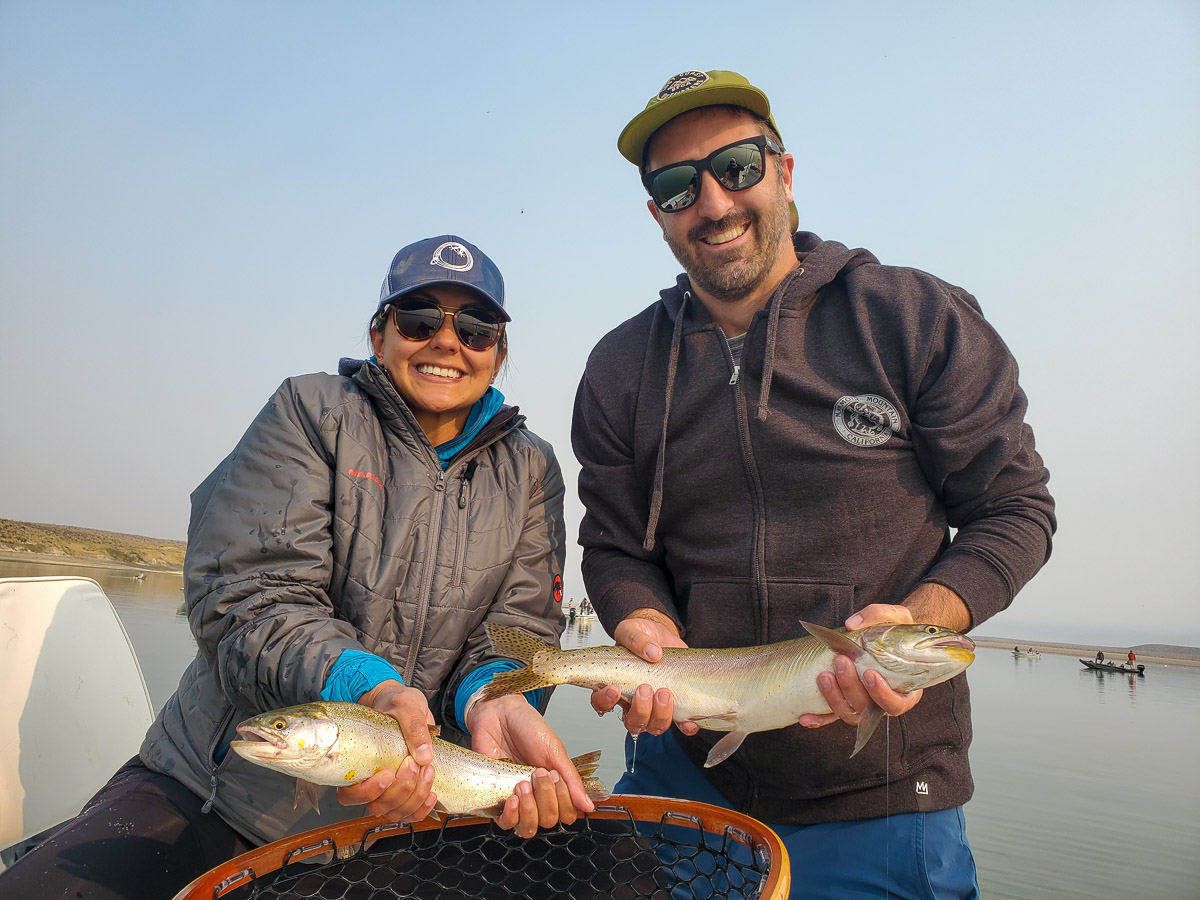 A smiling pair of fly fisherman holding a couple trout on a lake in a boat.